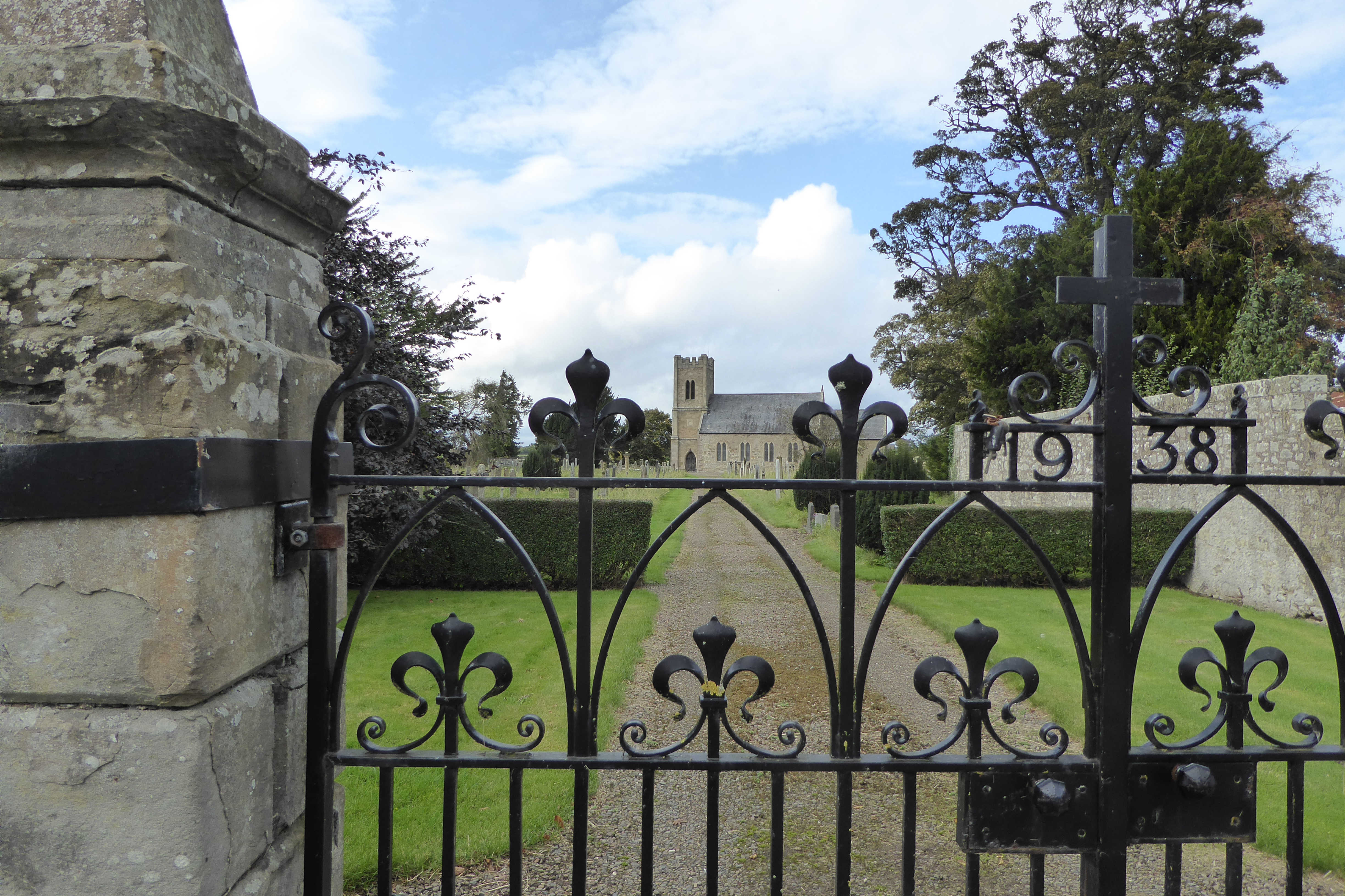 The Church of St Cuthbert and its wrought iron gates, which bear the date 1938